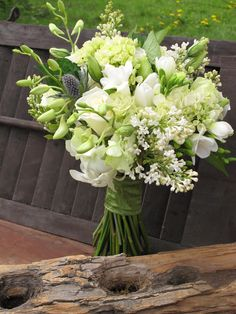 bouquet of white dendrobium orchids, lilacs, roses, freesia, lisianthus, hydrangea and thistle.