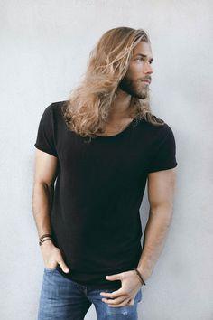 coupe de cheveux homme, t shirt noir et paire de jeans, bracelet marron pour homme, cheveux longs et blonds avec barbe