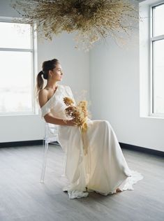 The concept behind this wedding inspiration came from the florist, who envisioned a blend of modern elegance and organic texture. Using foraged stems, she created a statement floral installation in golden hues.  The cascading gown brought a modern edge and was paired with exquisite and elegant gold-laced heels. We also pushed ourselves to balance the gallery with both classic poses and frames that are artistically fulfilling and a bit less traditional.    #wedding #weddingideas #golden #flowers
