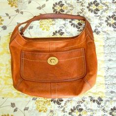 Coach Bag + BONUS POUCH Authentic Coach bag in a beautiful caramel colored leather. One outer pocket with classic gold coach hardware and additional pockets in the interior with space for your wallet, keys and cell phone. Lining is completely in tact. This bag is in used condition with some marks and scuffs throughout as seen in the pictures. The strap is darkened due to repetitive use since this was a favorite for some time. Price reflects condition and includes a BONUS coach wristlet that…
