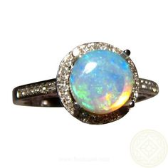 A pretty Opal and Diamond ring for women that is suitable as an engagement ring.  Shown in a 14k White Gold ring, there is a halo of pave Diamonds around the round Opal with Diamonds oround the top of the mount and on the band for a total of 75 Diamonds.  The Coober Pedy Crystal Opal is round in shape and shows bright Aqua Blue and Green colors in a pretty Pin Fire pattern.
