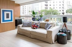 Decoração de apartamento com varanda com paredes de madeira, quadro azul e branco, sofá branco, plantas e adornos.