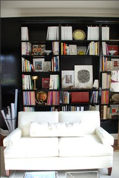 Love the black book shelves with the pop of color from everything on it.