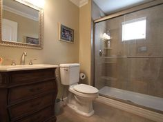 A curvaceous bathroom cabinet and a privacy window in the shower. Belmar, NJ