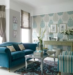 A fabulous paisley wallpapered accent wall creates a daring backdrop to opulently covered turquoise furnishings.