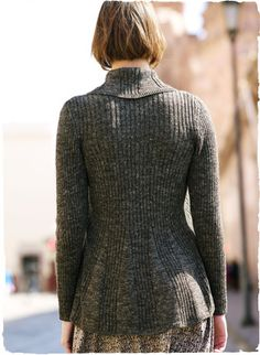 The homespun tweed cardigan—soft, tactile and contemporary—with a sculptural silhouette, angled ribs and sumptuous shawl collar. A single hook-and-eye closure cinches the waist. In baby alpaca (70%) and linen (30%).