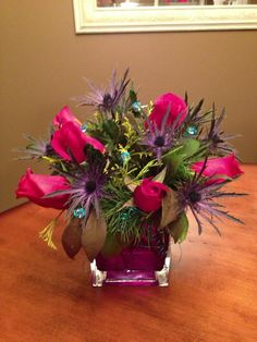 Thistle and roses in a cube vase with mixed evergreens cut around my yard....blue accent pins made with a diamond corsage pin and 24 gauge blue wire...wrapped the wire around the pin head then gently pulled the coils and separated around the gem making a cage around the pin head...poking the pins into the heavy evergreens....easy accent!
