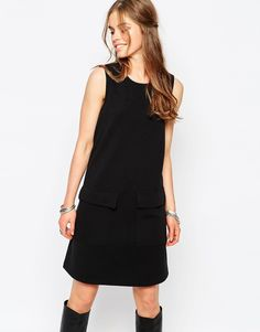 Black sleeveless shift dress with black boots--an updated 60's look
