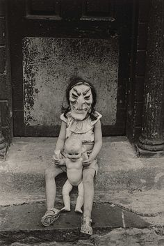 masked child with a doll, new york city. 1961. diane arbus.