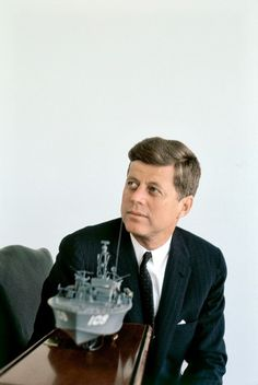 President Kennedy with model of the patrol boat that Kennedy served on during WWII. It was torpedoed and John Kennedy hailed a hero for his efforts to save his fellow crew men after the sinking. John Kennedy, Les Kennedy, Jacqueline Kennedy Onassis, Jaqueline Kennedy, Caroline Kennedy, Greatest Presidents, Us Presidents, American Presidents, Us History