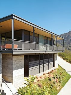 Modern steel-concrete-and-glass home with wraparound porch