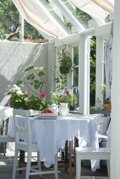 Love this conservatory.  Sweet curtains white table and pop of colour from the flowers