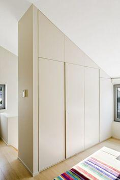 aménagement de combles avec une armoire de rangement blanche