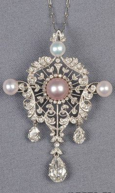 An Edwardian Platinum, Coloured Pearl, Pearl, and Diamond Pendant/Brooch. Set with a lavender pearl and three white button pearls, and suspending three pear-shape diamond drops, in an elaborate finely pierced mount set throughout with old single-cut diamond melee, millegrain accents, 2 in., together with a delicate paperclip chain. #Edwardian #pendant #brooch
