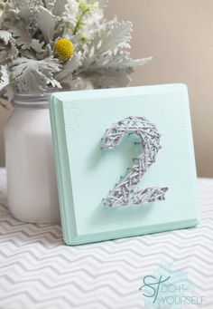 Wood, small nails, and lots of yarn is all you will need to make these diy string art table numbers for your wedding or home decor!