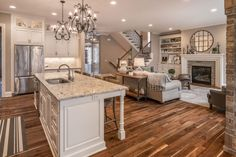 Beautiful wood flooring and custom design! This Great room is truly a dream! White Cabinetry, Granite countertops, trim work, wood floors, and lighting it the definition of extraordinary! - Memmer