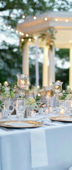 Candle holders and chargers against blue table cloth and white napkins