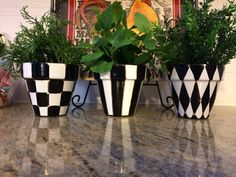 This striking set of 3 terra cotta pots, are hand painted in a black and white coordinating motif.  Harleqin, stripes and checks are