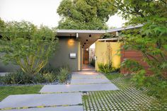 An ipe fence and a neon-yellow resin screen fashioned from recycled acrylic panels draw visitors toward the entrance to the Kreadens' renovated Eichler house.  Photo by: Daniel Hennessy