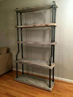 This is a freestanding shelving unit, with five shelf levels, three are 12 shelves, the lower two are 16. The pipe frame curves out under the lower 12 shelf, to support the larger shelves on the bottom. It also gives the shelf stability with the wider lower section. The two bottom shelves are