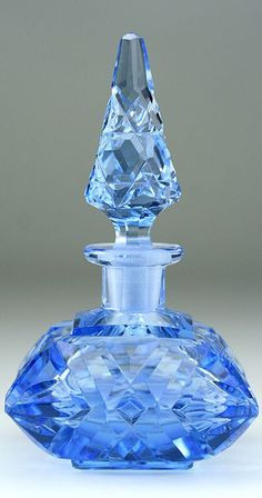 Deco blue crystal scent bottle with a hobnail cut spire stopper. The square cushion body is cut with geometric shapes, prisms, and blades. Circa 1930s,