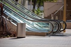 Orbit Litter & Recycling Receptacle shown in split-stream configuration with body in Stainless Steel with Seastone finish and custom powdercoat lid at Fashion Valley Mall, San Diego, California