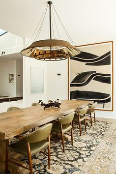 Dining room complete with raw edge dining table, leather dining chairs, chandelier and a vintage rug.