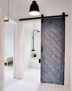 An old barn door from the South of France is an unexpected focal point in this bathroom. Contemporary Bathroom by MR.FRÄG