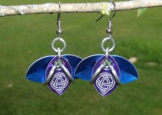 ETSY RhiannonscastlebTriquetras have been laser etched into the purple scales that adorn the center of these earrings. Complimented by two other petals created by a blue scale on either side.The Purple and Blue scales are Anodized Aluminum. All rings are saw cut Anodized Aluminum.