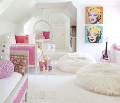 In Katie's attic-space playroom, walls painted Sherwin-Williams' West Highland White are enlivened with pink accessories, including pillows from John Robshaw Textiles and Pablo Mekis. A pair of French daybeds offer seating and sleep-over space, and juxtapose with reproduction art and Lucite elements from Soho Modern.