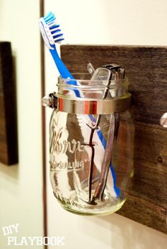 Whenever I see a clever jar-incorporating DIY, it speaks right to my glass hoarding heart. You'll love this DIY mason jar bathroom organizer! Rustic Bathroom Sinks, Western Bathrooms, Mason Jar Bathroom, Outhouse Bathroom, Bathroom Modern, Design Bathroom, Bathroom Wall, Bathroom Interior, Mason Jars