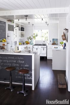 A blackboard in a kitchen makes it easy to write down reminders, grocery lists, or even an inspirational quote for everyone to see, such as this one in a Marin County, California, weekend house designed by Kim Dempster and Erin Martin. Subway tiles by Heath Ceramics. Gemini ceiling lights from Alfa. Paint is Benjamin Moore's Snow on the Mountain. - HouseBeautiful.com