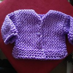 This is a loom knit baby cardigan made on a 5/8 inch gauge loom (purple KK hat loom, green KK long loom, red KK hat loom) with 24 to 28 pegs. It is perfect for an advanced beginner, and knits up quickly for the little one in your life. Sizing is for 6, 9, or 12 months.