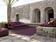 Love the plum furniture and rug paired with the concrete...rich and minimal