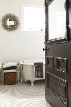 bathroom, love the vintage tub and black door