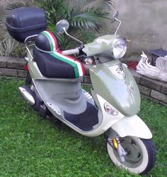 Genuine Buddy Italia Scooter seat cover - Italian Racing Stripe.   This dreamy scooter belongs to Terry  of the Royal Bastards Scooter Club.  We think this snazzy Italian Racing Stripe looks great on her scooter, and we love how it matches her helmet!  You only get a slight hint from this picture but Terry has an amazing little courtyard garden that she calls her escape.  Love it!  #CheekySeats