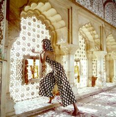 Veruschka standing in the Jas Mandir wearing hooded halter pyjamas for the evening, in black with gold polka-dots, by Trigere, photo by Henry Clarke, Jaipur, India, 1968