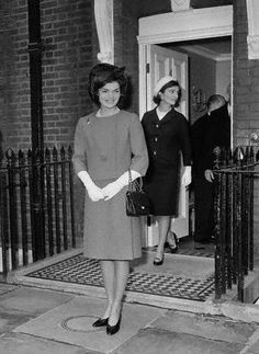 Jackie Kennedy leaves her sister's home to drive to Buckingham Palace to lunch with Queen Elizabeth. Mrs. Kennedy is wearing a petunia pink suit, high heeled black shoes, and a mink hat with black band. March 28, 1962