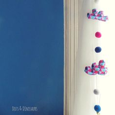 Cute and colourfull handmade cloud and raindrop mobile with felt balls and a ringing bell .Makes a lovely window or door decoration for your