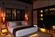 Grand bedroom with an Arabic carpet on floor, lighted by dim yellow lights with artistic dividers.