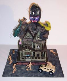 From Misguided Designs Hand Painted Gifts. A haunted house made from paper with a knit octopus, toys and painted people in the windows.