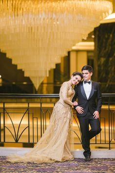 Bride and groom in champagne wedding gown and classic black suit posing against dramatic chandelier // If you thought Yoska and Nariza's Bali nuptials were one for the books, just wait until you see the floating dais at their nikah (or solemnization) in Kuala Lumpur! The couple's Malaysia wedding celebrations continued with a Gatsby-themed dinner reception at The Majestic Hotel Kuala Lumpur, shot by Haniff Hazim ...