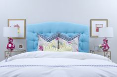 Fantastic bedroom with light blue walls framing turquoise blue tufted headboard accented with modern floral pillows and chartreuse Greek key lumbar pillows and white and blue bedding flanked by antique brass bedside tables with glass tops and white and pink brushstroke lamps.