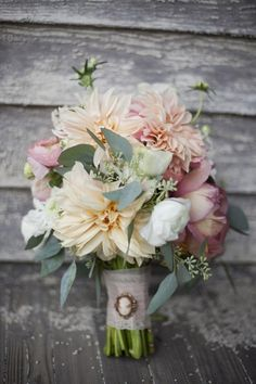 Shades of pink to peach accented with the gray blue of seeded eucalyptus in this bride's bouquet with the cameo detail