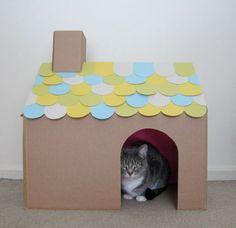 Esse terceiro modelo de casinha para gatos é um dos mais simples de fazer em casa, pois basta cortar a abertura para o gatinho entrar, e, em seguida, caprichar na decoração do telhado, que fica um charme com vários recortes de papel colorido. Para completar, você pode adicionar uma chaminé de papelão, item super bem vindo para embelezar ainda mais a casinha.
