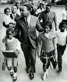 Dr. Martin Luther King Jr. walks between seven-year-old Eva Gracelemon (left) and 10-year-old Aritha Willis as he escorts the school children to formerly all-white schools in Grenada, Mississippi. 9/20/66