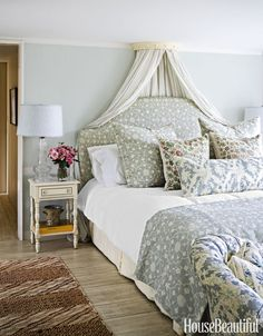 In the master bedroom, Ireland's Sheer Stripe linen in Blue is draped from a coronet that the designer found at McKinney & Co. in London years ago. The headboard is covered in her Abu linen.