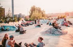 A crowd of twenty somethings sit in a skate park during the Flow Festival.
