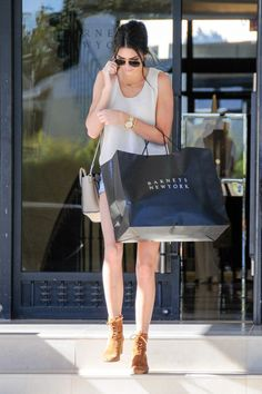 In cutoff denim shorts, suede lace-up booties and a mini Celine handbag while shopping at Barneys in Los Angeles.