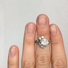 Custom stone cluster ring with a 1.47 carat M/VS1 jubilee cut white diamond. Surround with Sri Lankan bicolor sapphires, Montana sapphire, and peach sapphire. Set in 14k yellow gold. MOCIUN